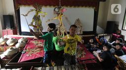 Anak-anak berlatih mendalang wayang kulit di Sanggar Nirmalasari, Cinere, Depok, Jawa Barat, Minggu (9/2/2020). Sanggar yang berdiri sejak tahun 1987 ini melatih para siswa setiap hari Minggu. (merdeka.com/Arie Basuki)