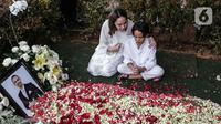 Bunga Citra Lestari atau BCL bersama anaknya Noah Sinclair duduk di samping makam Ashraf Sinclair di San Diego Hills, Karawang, Jawa Barat, Selasa (18/2/2020). Ashraf Sinclair mengembuskan napas terakhir pukul 04.51 WIB pagi tadi. (Liputan6.com/Faizal Fanani)