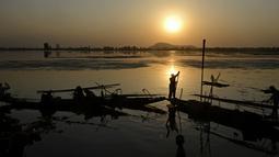 Aktivitas nelayan Kashmir saat matahari terbenam di danau Dal di Srinagar, India (12/9). Danau Dal yang luas dan bening. Diatasnya terhampar gerombolan daun bunga lotus. (AFP Photo/Tauseef Mustafa)
