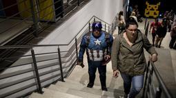 Seorang cosplayer berpakaian seperti karakter Marvel Captain America berdiri  di tangga selama International Comic Con di Kyalami Race Course, Johannesburg, Afrika Selatan (14/9). Comic Con digelar pada tahun 1970. (AFP Photo/Marco Longari)