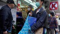 Seorang pria dengan mengenakan masker wajah seusai membeli kertas tisu di luar apotek di Hong Kong, Kamis (6/2/2020). Di tengah kelangkaan masker wajah untuk melindungi terhadap wabah virus corona, tisu toilet tiba-tiba juga menjadi salah satu barang yang langka di Hong Kong. (AP/Vincent Yu)