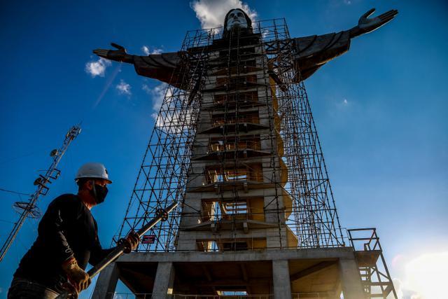 Seorang pekerja terlihat di depan patung Kristus yang sedang dibangun di Encantado, negara bagian Rio Grande do Sul, Brasil, pada 9 April 2021. Proyek dengan dana sebesar 350.000 dolar AS atau setara Rp5,1 miliar direncanakan untuk selesai pada tahun ini. (SILVIO AVILA/AFP)