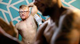 Charles Bennett dari San Francisco mempersiapkan diri di belakang panggung kompetisi International Association of Trans Bodybuilders di Atlanta, 6 Oktober 2018. Moore yang terlahir sebagai perempuan melakukan transisi dua tahun lalu. (AP/David Goldman)