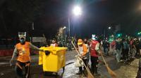 Pasukan Linmas dari Kota Surabaya membersihkan kotoran sisa-sisa sampah demo UU Cipta Kerja pada Kamis, 8 Oktober 2020. (Foto: Liputan6.com/Dian Kurniawan)