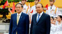 PM Jepang Yoshihide Suga (kiri) berjalan bersama dengan PM Vietnam Nguyen Xuan Phuc meninjau pasukan kehormatan di Istana Kepresidenan, di Hanoi, Vietnam, Senin (19/10/2020). Yoshihide Suga melakukan kunjungan resmi ke Vietnam hingga 20 Oktober 2020. (Kham/Pool Photo via AP)
