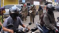Petugas Satpol PP mengimbau warga untuk menggunakan masker dan menjaga jarak di Pasar Lama, Kota Tangerang, Banten, Sabtu (9/6/2020). Pemkot Tangerang melakukan penegasan pada PSBB tahap dua dengan menugaskan petugas di keramaian guna memutus rantai penyebaran COVID-19.  (Liputan6.com/Angga Yuniar)