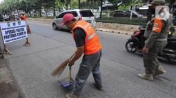 Seorang pelanggar menyapu jalanan saat terjaring Operasi Yustisi Protokol COVID-19 di Jati Padang, Jakarta Selatan, Kamis (17/9/2020). Operasi itu untuk menegakan penerapan protokol kesehatan, terutama dalam penggunaan masker guna menekan penyebaran virus corona. (merdeka.com/Arie Basuki)