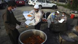 Sukarelawan menyiapkan makanan berbuka puasa gratis untuk orang-orang yang membutuhkan selama bulan puasa suci Ramadan di Kabul, Afghanistan, Kamis (7/5/2020). Muslim di seluruh dunia melewati Ramadan tahun ini di tengah pandemi virus corona COVID-19 dan PHK. (AP Photo/Rahmat Gul)