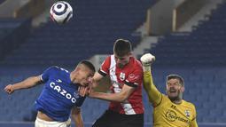 Kiper Southampton, Fraser Forster (kanan) meninju bola dari ancaman striker Everton, Richarlison (kiri) dalam laga lanjutan Liga Inggris 2020/21 pekan ke-26 di Goodison Park, Liverpool, Senin (1/3/2021). Southampton kalah 0-1 dari Everton. (AP/Gareth Copley/Pool)