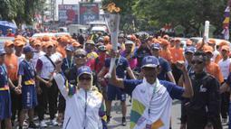 Pebalap sepeda legendaris Indonesia, Sutiyono, bersiap mengikuti pawai obor Asian Games XVIII di Lampung, Rabu (8/8/2018). Sebanyak 53 kota di Indonesia akan dilalui oleh obor Asian Games. (Bola.com/Reza Bachtiar)