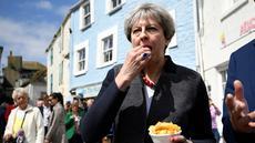 Perdana Menteri (PM) Inggris, Theresa May mencicipi beberapa keripik saat berhenti untuk kampanye di Mevagissey, Cornwall, Selasa (2/5). Theresa May melakukan kampanye dengan berkeliling jalanan di Cornwall. (Dylan Martinez/PA via AP)