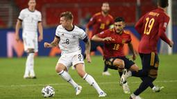 Gelandang Jerman, Toni Kroos, berebut bola dengan gelandang Spanyol, Oscar Rodriguez, pada laga Nation League di Mercedes-Benz Arena, Berlin, Jumat (4/9/2020) dini hari WIB. Jerman bermain imbang 1-1 atas Spanyol. (AFP/Thomas Kienzle)