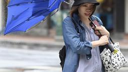 Seorang wanita membawa payungnya yang rusak saat berjalan melawan angin kencang yang ditimbulkan oleh topan Lekima di Taipei, Taiwan (9/8/2019). Topan  tersebut dinilai sebagai yang terkuat menghantam Taiwan di tahun ini. (AFP Photo/Sam Yeh)