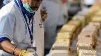 Seorang koki menyelesaikan kue sepanjang 6,5 km untuk kue terpanjang dunia, di Thrissur di negara bagian Kerala, India selatan (15/1/2020). Ratusan pembuat roti dan koki di India selatan membuat kue terpanjang di dunia. (AFP/Arun Sankar)