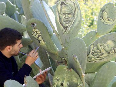 Seniman muda Palestina, Ahmad Yasin saat melukis tanaman kaktus di desa Tepi Barat Aseera Ashmaliya dekat Nablus, (31/3).Berbagai gambar unik dituangkan Ahmad Yasin kedalalam sejumlah tangkai kaktus.  (REUTERS / Abed Omar Qusini)
