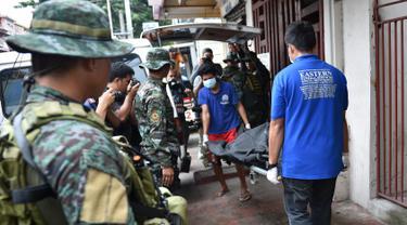 Personel polisi Filipina mengamati pekerja yang membawa jasad seorang napi yang tewas akibat kerusuhan di sebuah penjara di Filipina, Rabu (28/9). Selain menewaskan satu anggota geng narkoba, kerusuhan itu juga melukai tiga napi lainnya. (TED Aljibe/AFP)