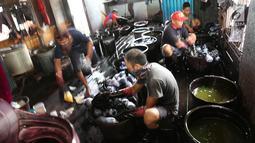 Pekerja mewarnai kain sasirangan di kawasan Banjarmasin, Kalimantan Selatan, Senin (26/3). Proses pewarnaan kain ini dengan menggunakan bahan perintang seperti tali, benang atau sejenisnya menurut corak-corak tertentu. (Liputan6.com/Immanuel Antonius)