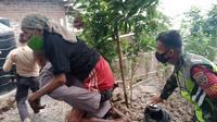 Petugas mengevakuasi seorang lansia yang bermukim di sekitar Gunung Ili Lewotolok. Gunung Ili Lewotolok mengalami peningkatan aktivitas vulkanik sejak Minggu, (29/11/2020). (Liputan6.com/ Ola Keda)