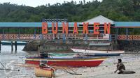 Warga duduk di pinggir pantai dekat tulisan 'Welcome to Bunaken' di Pulau Bunaken, Manado, Sabtu (17/12). Pemprov Sulut gencar melakukan promosi pariwisata dengan tujuan mendatangkan turis sebanyak mungkin hingga ke Tiongkok. (Liputan6.com/Fery Pradolo)