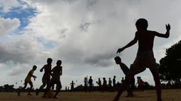 Anak-anak Rohingya bermain sepak bola di kamp pengungsi Kutupalong di Ukhia, Bangladesh, 19 Juli 2018. Bendera Argentina dan Brasil bahkan masih berkibar berdampingan dengan bendera Bangladesh di kamp pengungsi terbesar di dunia. (AFP/Munir UZ ZAMAN)