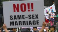 Seorang warga membentangkan poster anti-gay saat acara parade 'Gay Pride' di Seoul, Korea Selatan (15/7). Selain mereka yang merayakan parade LGBT, ada juga kelompok anti-gay yang menggelar aksi tandingan. (AP Photo / Ahn Young-joon)