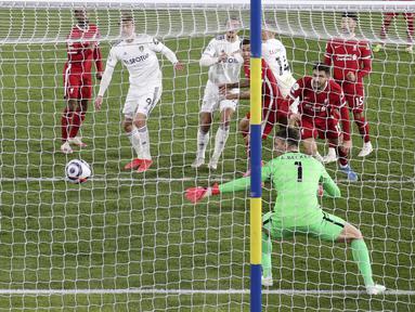 Pemain Leeds United Diego Llorente (ketiga kanan) mencetak gol ke gawang Liverpool pada  pertandingan Liga Inggris di Stadion Elland Road, Leeds, Inggris, Senin (19/4/2021). Pertandingan berakhir dengan skor 1-1. (Clive Brunskill/Pool via AP)