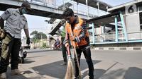 Seorang warga membersihkan jalanan saat menjalani hukuman sosial pelanggar PSBB di area Pasar Kramat Jati, Jakarta, Rabu (17/6/2020). (merdeka.com/Iqbal S. Nugroho)