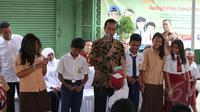 Presiden Jokowi berdialog dengan pelajar saat pembagian Kartu Indonesia Sehat (KIS), Kartu Indonesia Pintar dan Kartu Keluarga Sejahtera (KKS) kepada masyarakat di Penjaringan, Jakarta, Rabu (13/5). (Liputan6.com/Faizal Fanani)