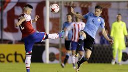 Gelandang Uruguay, Federico Valverde, berebut bola dengan bek Paraguay, Jorge Moreira, pada laga kualifikasi piala dunia 2018 di Stadion Defensores del Chaco, Rabu (6/9/2017). Uruguay menang 2-1 atas Paraguay. (AP/Jorge Saenz)