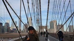 Orang-orang berjalan melintasi Jembatan Brooklyn di New York, 3 Desember 2018. Jembatan itu menjadi salah satu tujuan turis, lokasi pembuatan film maupun warga kota yang hendak menikmati suasana Brooklyn-Manhattan dari sisi berbeda. (AP/Wong Maye-E)