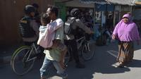 Masyarakat lalu lalang saat polisi bersepeda berpatroli di kawasan wisata Pulau Gili Air, Lombok, Nusa Tenggara Barat (NTB), Sabtu (11/8). Patroli dilakukan setelah gempa 7 skala Richter melanda Lombok pada 5 Agustus lalu. (Adek BERRY/AFP)