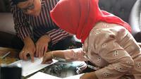 Berbusana adat Jawa, Gubernur Jawa Tengah Ganjar Pranowo mengambil rapor anaknya di SMAN 3 Semarang, Kamis (19/12). (Liputan6.com/ Istimewa)