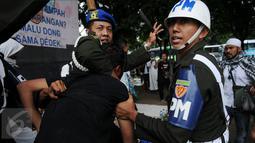Seorang pria yang diduga provokator dalam aksi damai 2 Desember ditangkap oleh polisi Militer Angkatan Laut di kawasan Monas, Jakarta, Jumat (2/12). Pria itu tertangkap tangan membawa golok saat aksi damai tengah berlangsung. (Liputan6.com/Gempur M Surya)