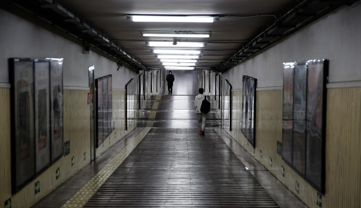 Komuter melewati terowongan menuju stasiun kereta bawah tanah di Beijing, China, Senin (17/2/2020). Wabah virus corona atau COVID-19 menyebabkan beberapa kota besar di China menjadi sepi, salah satunya Beijing. (AP Photo/Andy Wong)