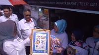 Kepala BPOM Penny K.Lukito memberikan poster sosialisasi pengolahan pangan aman ke salah satu pedagang pempek di Pasar Kuliner 26 Ilir Palembang (Liputan6.com / Nefri Inge)
