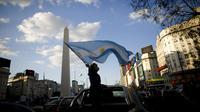 Seorang wanita memegang bendera Argentina selama berunjuk rasa menentang berbagai masalah termasuk kebijakan ekonomi pemerintah dan negara untuk melawan penyebaran COVID-19 di Buenos Aires, Argentina, Senin (12/10/2020). (AP Photo/Natacha Pisarenko)