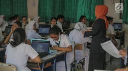 Pengawas ujian membacakan tata tertib Ujian Nasional Berbasis Komputer (UNBK) saat pelaksaan UNBK di SMP Negeri (SMPN) 1, Cikini, Jakarta, Senin, (22/4). Sebanyak 4.279.008 siswa mengikuti UNBK tingkat SMP dan MTS yang dilaksanakan mulai 22 April hingga 25 April. (Liputan6.com/Faizal Fanani)
