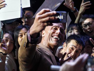 Aktor Dwayne Johnson berswafoto bersama penggemar selama acara red carpet dalam premiere film 'Fast & Furious: Hobbs & Shaw' di Beijing, China, Senin (5/8/2019). Hobbs and Shaw menempatkan dua aktor laga papan atas, Jason Statham dan Dwayne Johnson sebagai pemeran utama. (AP Photo/Andy Wong)