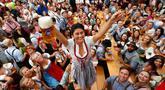 Seorang wanita merayakan pembukaan festival bir Oktoberfest ke-185 di Munich, Jerman, Sabtu (22/9). Festival bir terbesar di dunia ini diselenggarakan mulai 22 September hingga 7 Oktober 2018. (AP Photo/Matthias Schrader)