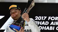 Valtteri Bottas mengangkat trofi juara seetalah finis pertama pada balapan F1 Abu Dhabi di Yas Marina circuit , (26/11/2017). (AFP/Giuseppe Cacace)