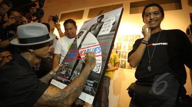 "Drummer grup musik Superman Is Dead, Jrx (kiri) menandatangani foto saat pameran fotografi ""Laut Luka Blues"" di Galeri Foto Jurnalistik Antara , Jakarta, Jumat (22/5/2015). 51 karya foto karya Ismar Patrizki dipamerkan. (Liputan6.com/Faizal Fanani)"