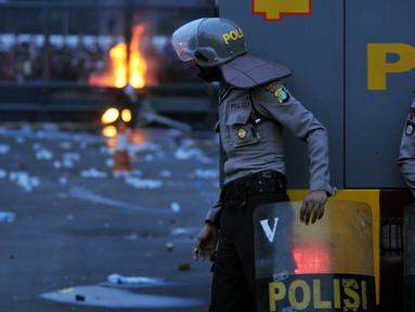 Seorang petugas mengamati aksi mahasiswa memperingati Hari Sumpah Pemuda di depan Gedung DPR, Senayan, Jakarta, Rabu (28/10/2015). Dalam aksinya para mahasiswa membakar ban. (Liputan6.com/Johan Tallo)