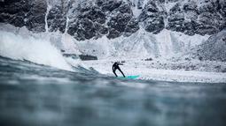 Seorang surfer menaiki papanya berselancar di melewati ombak di Unstad, Norwegia Utara (10/3). Peselancar ini menaklukan ombak dengan konidisi suhu minus 13 derajat Celsius. (AFP Photo/Olivier Morin)