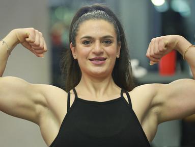 Binaragawan Yordania, Dana Sombouloglu menunjukkan ototnya selama sesi latihan di gym di ibukota Amman, pada 29 Januari 2020. Perempuan 26 tahun ini memiliki tekad kuat untuk membuktikan bahwa perempuan Yordania bisa jadi binaragawan. (AFP/Khalil Mazraawi)