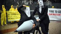 Dua aktivis berpose dengan rudal tiruan dengan memakai topeng Presiden AS, Donald Trump dan Pemimpin Korut, Kim Jon-un di Kedubes Korea Utara di Berlin, Jerman (13/9). Mereka menutut penghapusan senjata nuklir. (AFP Photo/dpa/Britta Pedersen/Germany Out)