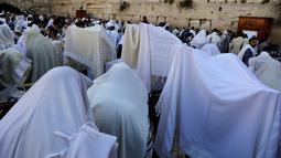 Ribuan umat Yahudi menggelar doa di Tembok Barat Kota Tua Yerusalem, Senin (2/4). Ritual ini berlangsung delapan hari selama libur Paskah. (MENAHEM KAHANA/AFP)
