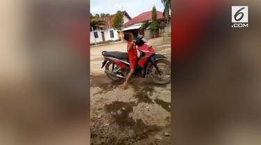 Enggak mau kalah, seorang bocah ikut mencoba aksi standing yang sebelumnya dilakukan temannya. Bukannya berhasil, aksi bocah tersebut malah gagal karena terpental dari motor.