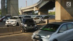 Sejumlah kendaraan menerobos pagar pembatas jalan tol di KM 30 Tol Jakarta - Cikampek, kawasan Cikarang, Jawa Barat, Minggu (9/6). Kemacetan yang terjadi di sepanjang jalur tersebut menyebabkan sebagian kendaraan nekat menerobos pagar pembatas untuk berpindah jalur. (Liputan6.com/Immanuel Antonius)