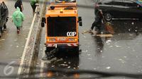 Kendaraan penyapu jalan diterjunkan untuk membantu membersihkan jalan Medan Merdeka Barat dari ceceran sampah usai perayaan hari Buruh Internasional 2017, Jakarta, Senin (5/1). (Liputan6.com/Helmi Fithriansyah)