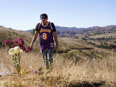 Anthony Calderon mengenakan jersey Kobe Bryant di lokasi kecelakaan helikopter yang menewaskan Bryant, putrinya Gianna, dan tujuh orang lainnya satu tahun lalu di Calabasas, California, Amerika Serikat, Selasa (26/1/2021). (AP Photo/Marcio Jose Sanchez)